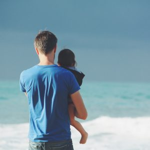 dad holding daughter at the beach