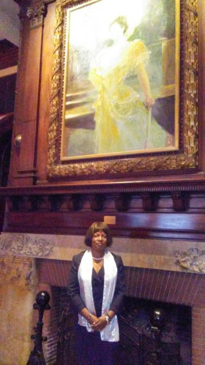 woman posing in front of a large framed painting over a fireplace