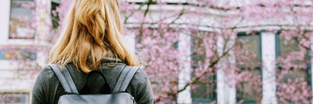 young woman in front of cherry blossoms wearing backpack facing building
