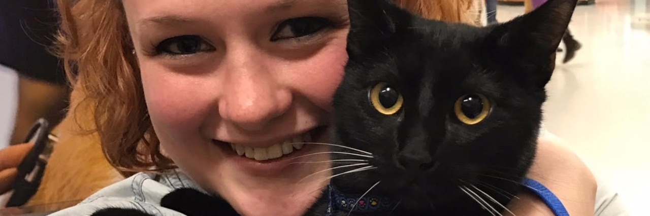 contributor smiling while holding emotional support animal black cat