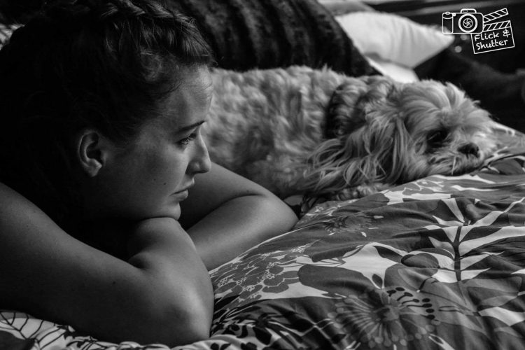 woman resting chin on arms and looking at dog