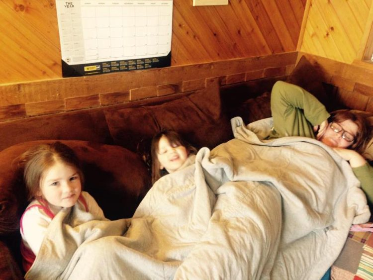 woman on couch with two little girls under blanket