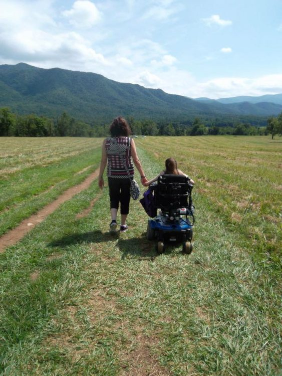 woman in wheelchair holding hands with mom, facing mountain
