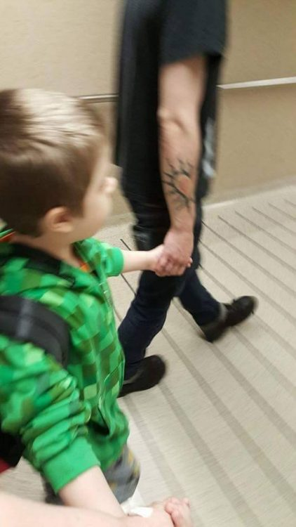 man holding hands with young boy