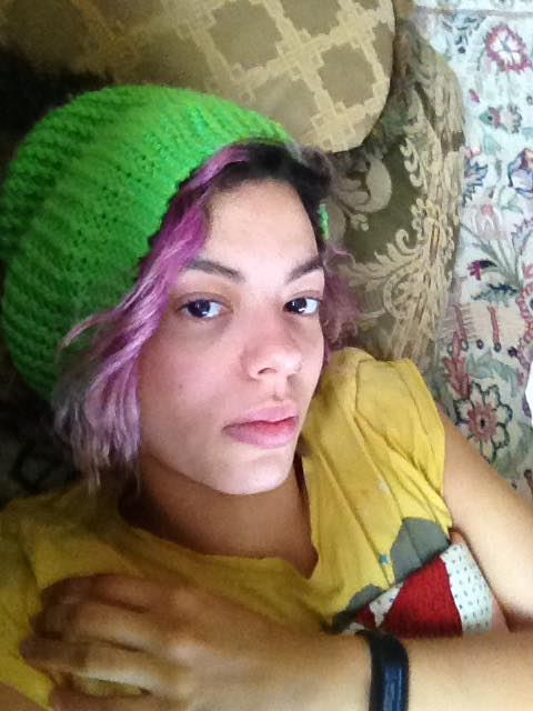 woman lying down wearing green hat