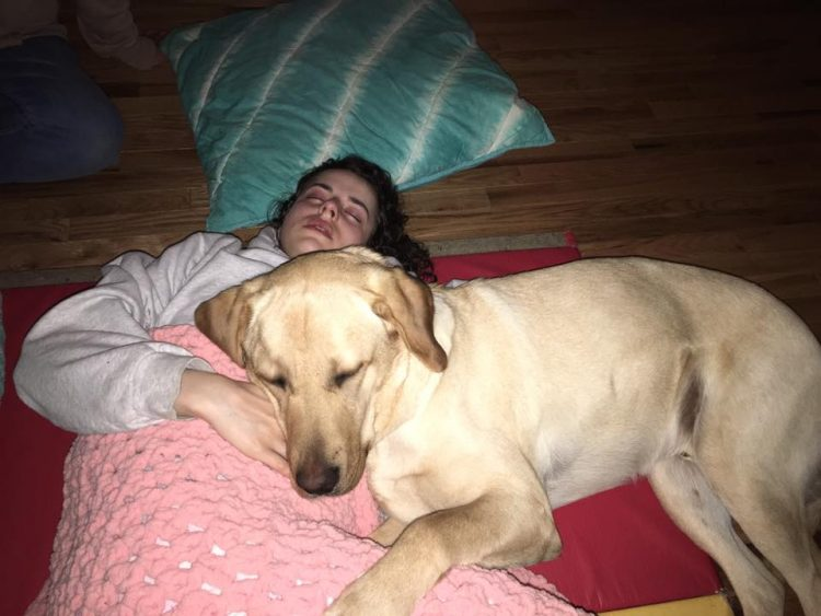 girl lying on floor with dog snuggling her