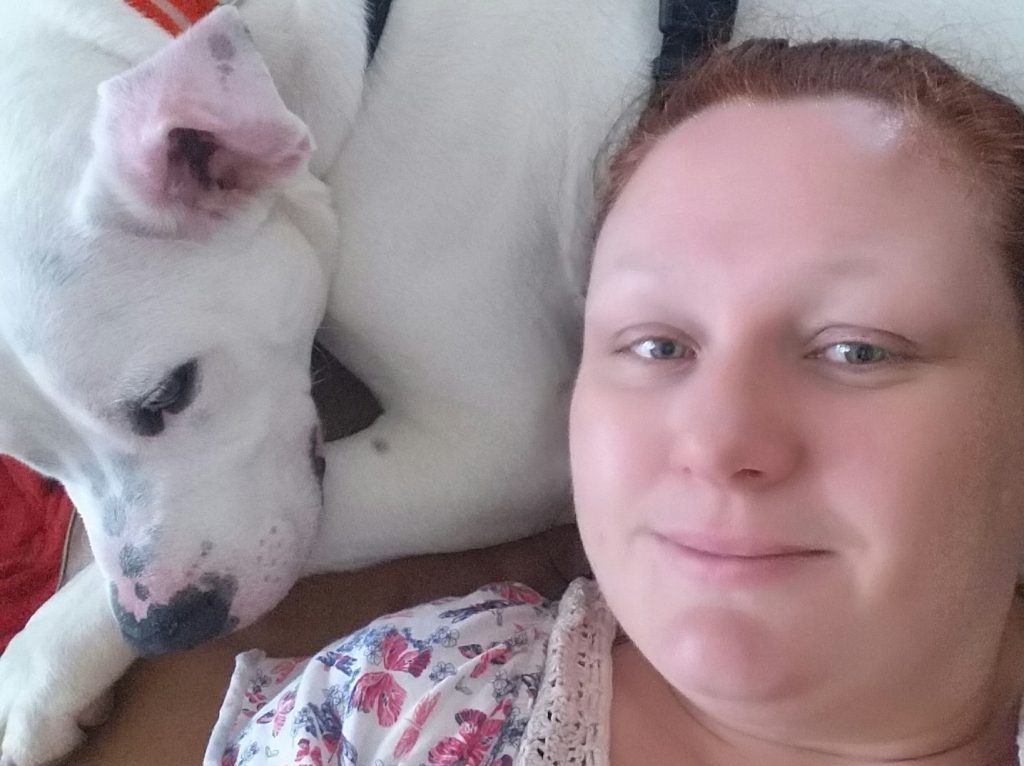 woman lying down with white american bulldog lying beside her with head resting on paw