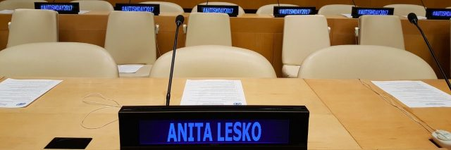 UN tables and chairs with a digital nameplate reading Anita Lesko and digital name plates on tables in the background that say Autism Day 2017