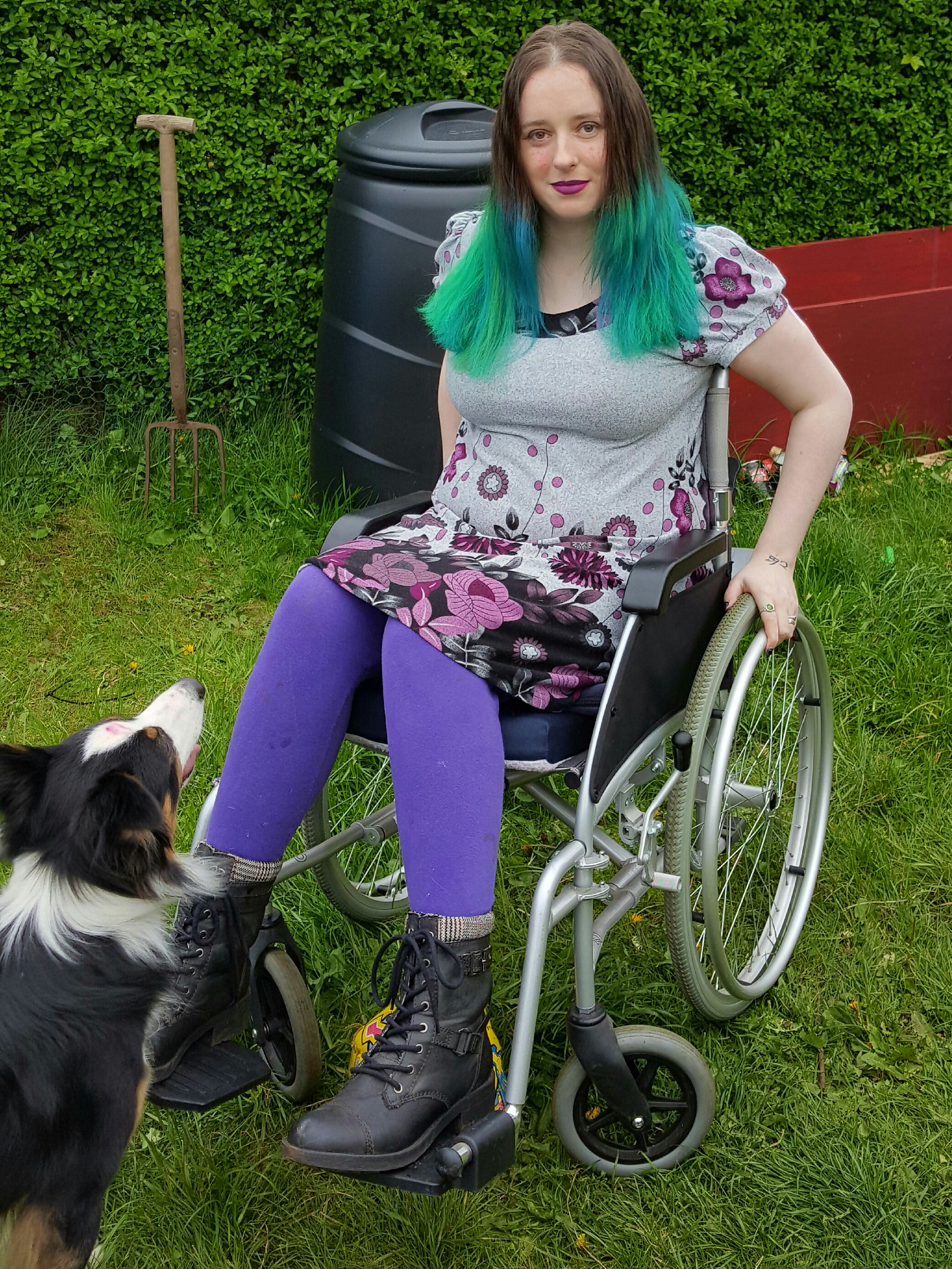 woman sitting outside in a wheelchair next to a dog