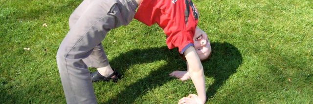 young boy doing a backbend outside