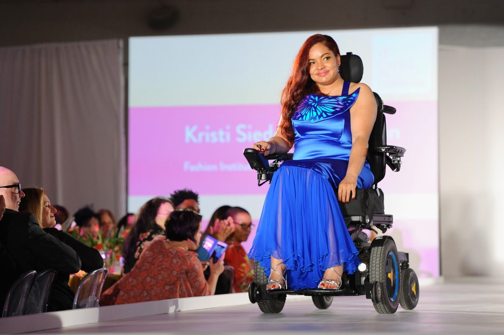 A model in blue dress using a power wheelchair.