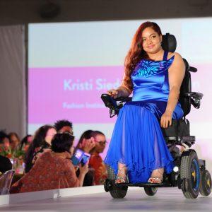 A model in blue dress using a power wheelchair.