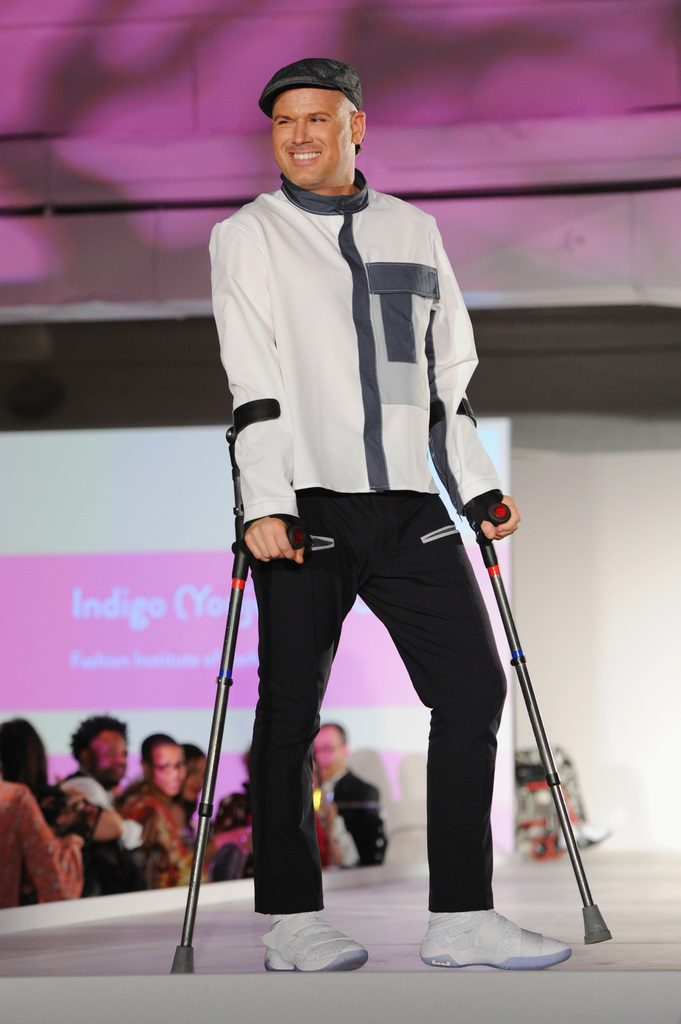 A model walks the runway with crutches, showcasing a design.