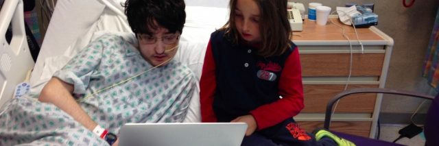 Two kids, one a hospital patient and one a visitor, sitting on hospital bed, looking at laptop