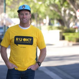 A man wearing an R U OK? t-shirt standing in the streat
