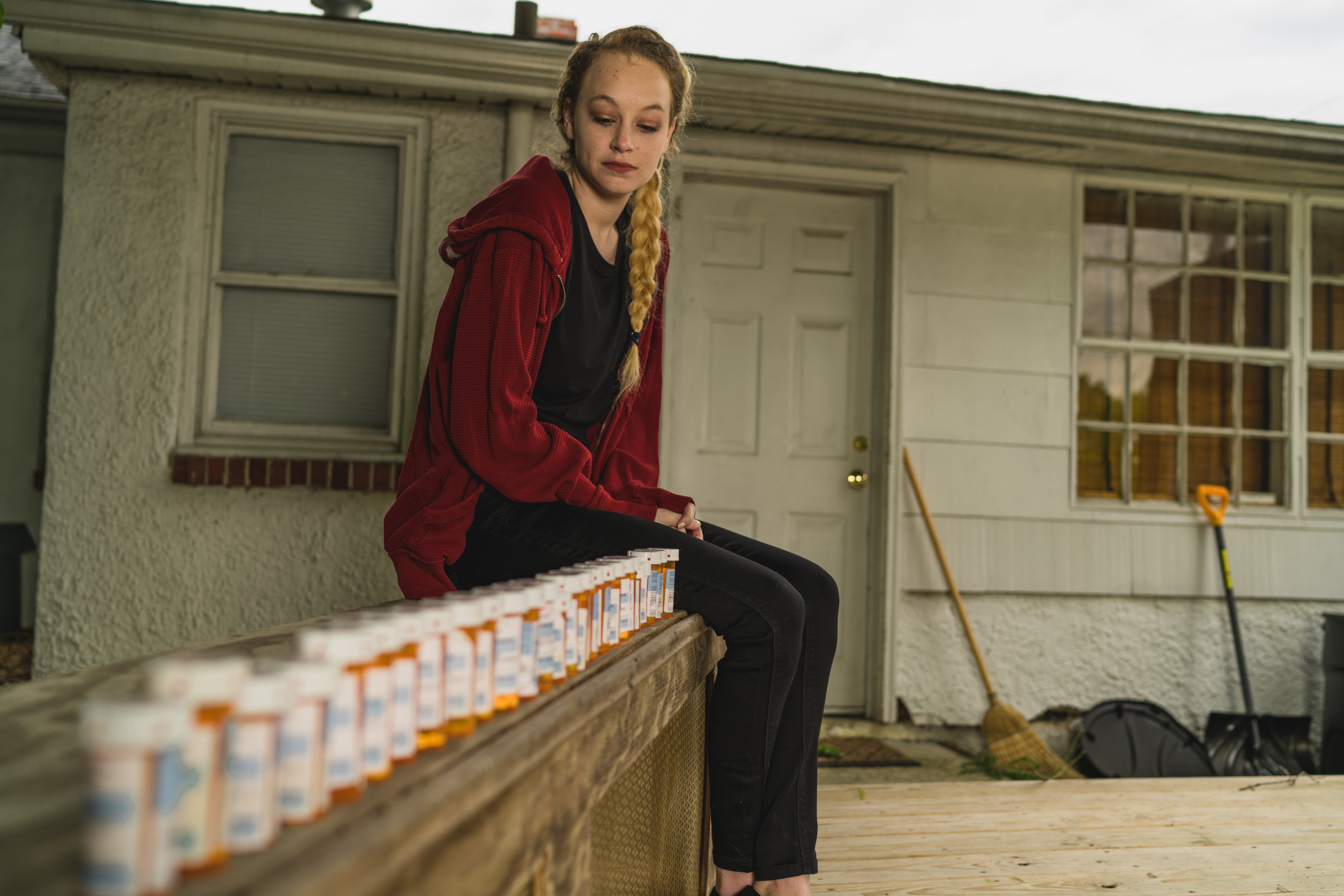 wide shot of woman on bench with medication bottles