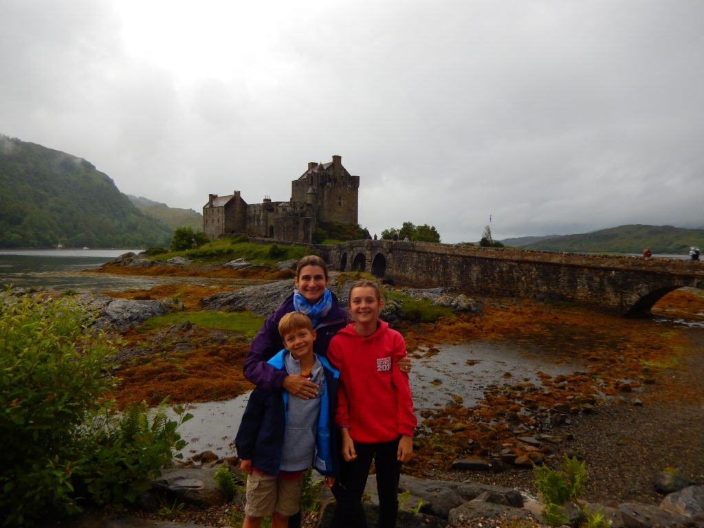 mother and two children at eilean donan castle in scotland