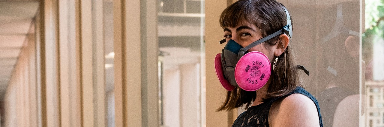 woman wearing a face mask doing wall squats after receiving an infusion