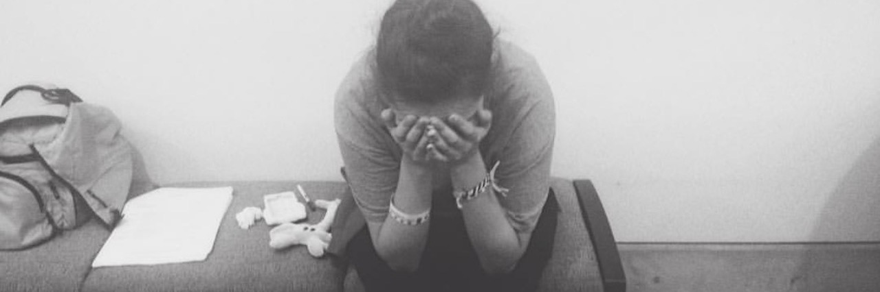 black and white photo of a woman sitting on a table looking distraught