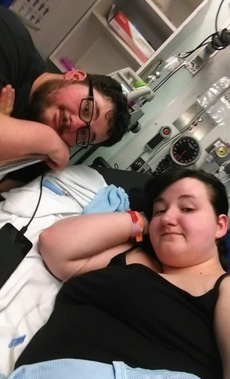 sophie in hospital bed with boyfriend next to her