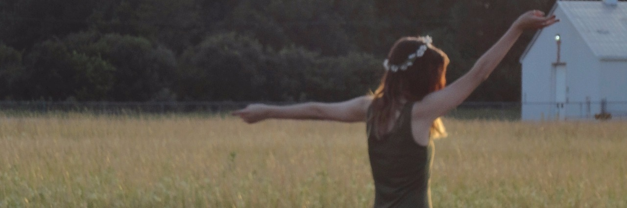 woman raising arms in field