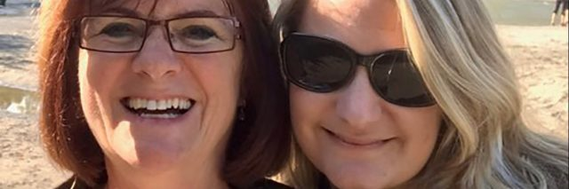 two women in sunshine smiling with rocks and greenery behind them, one of them wearing sunglasses