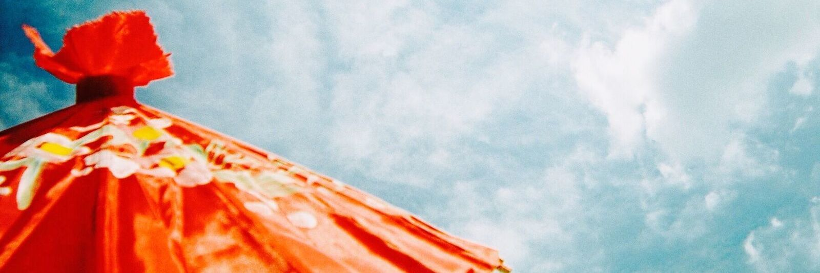 orange umbrella against a blue sky