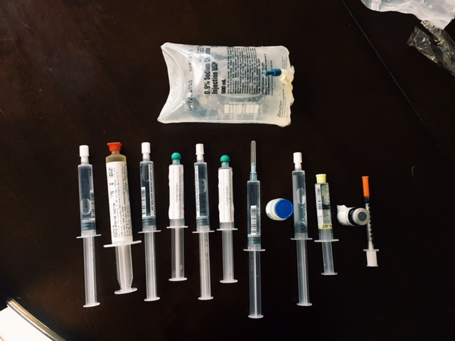 row of needles, injections and bag of iv fluids