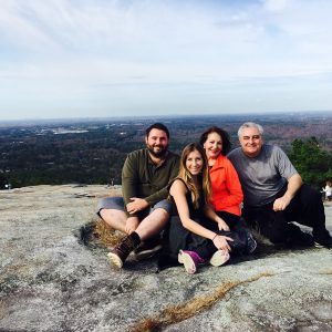 family sitting on the top of a mountain after a hike