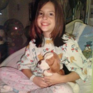 young girl sitting in a hospital bed with a stuffed animal