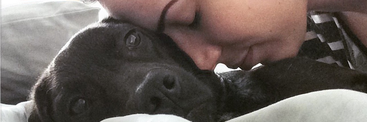 image of young woman resting head lovingly on black labrador dog