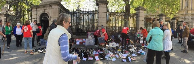 rows of shoes on ground in front of government building gate