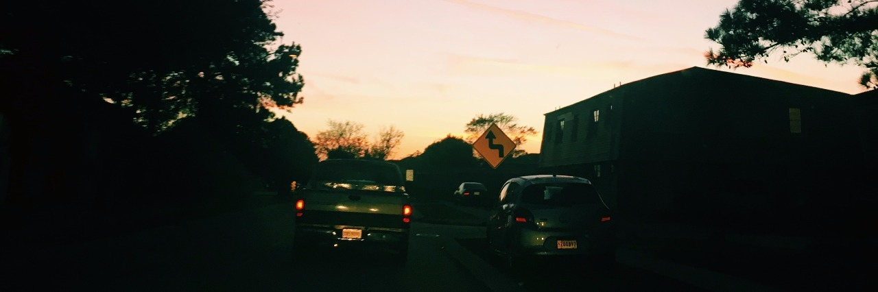 sunset above traffic and suburban area