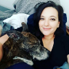 woman smiling and lying in bed with her dog