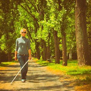 Blind woman walking in a park.