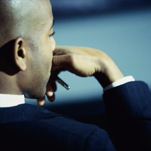 side portrait of businessman with hand resting in front of mouth, deep in thought