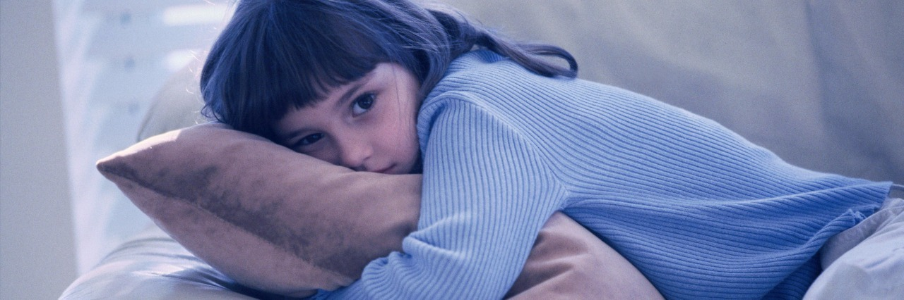 young girl hugging cushoin on the sofa