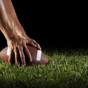 Hands on football in grass.