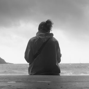 Woman sitting on front of the sea on an overcast day