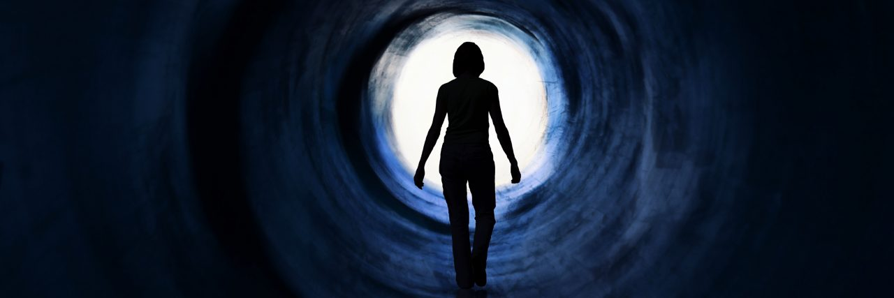 Woman walking towards the light at the end of the tunnel