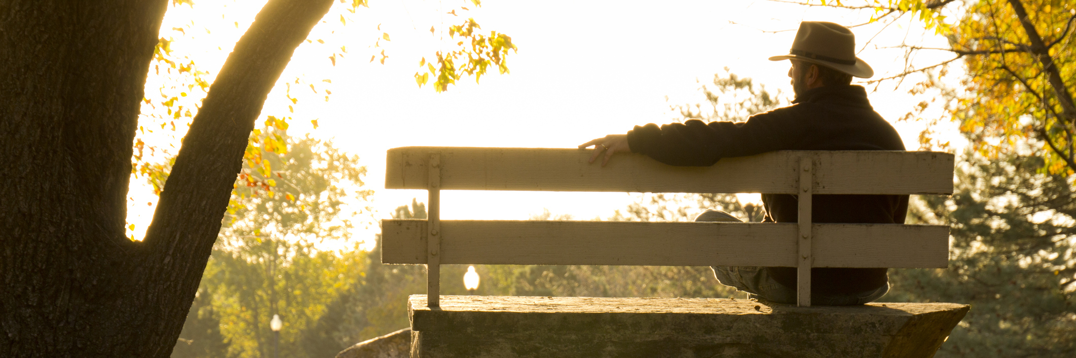 man sitting on a park bench at sunrise