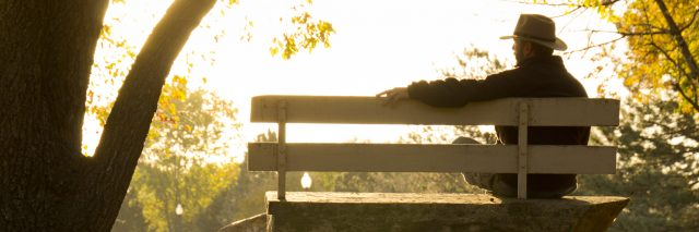 man sitting on a park bench at sunrise