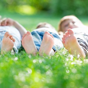 Group of happy children lying on green grass.
