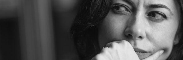 Close-up portrait of a pensive woman. low key.