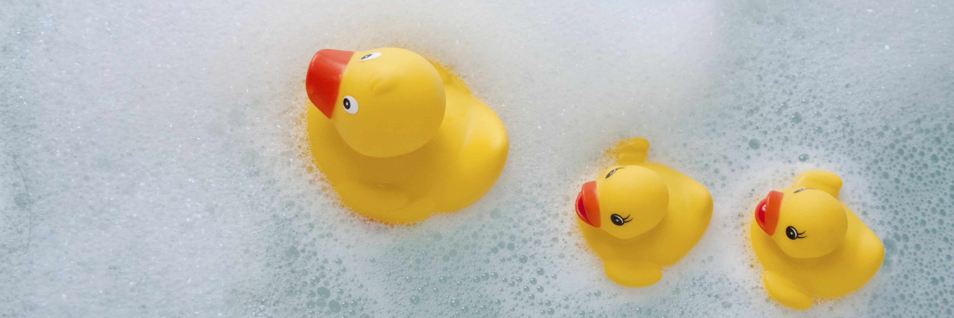 3 rubber ducks of different sizes floating in soapy bath water