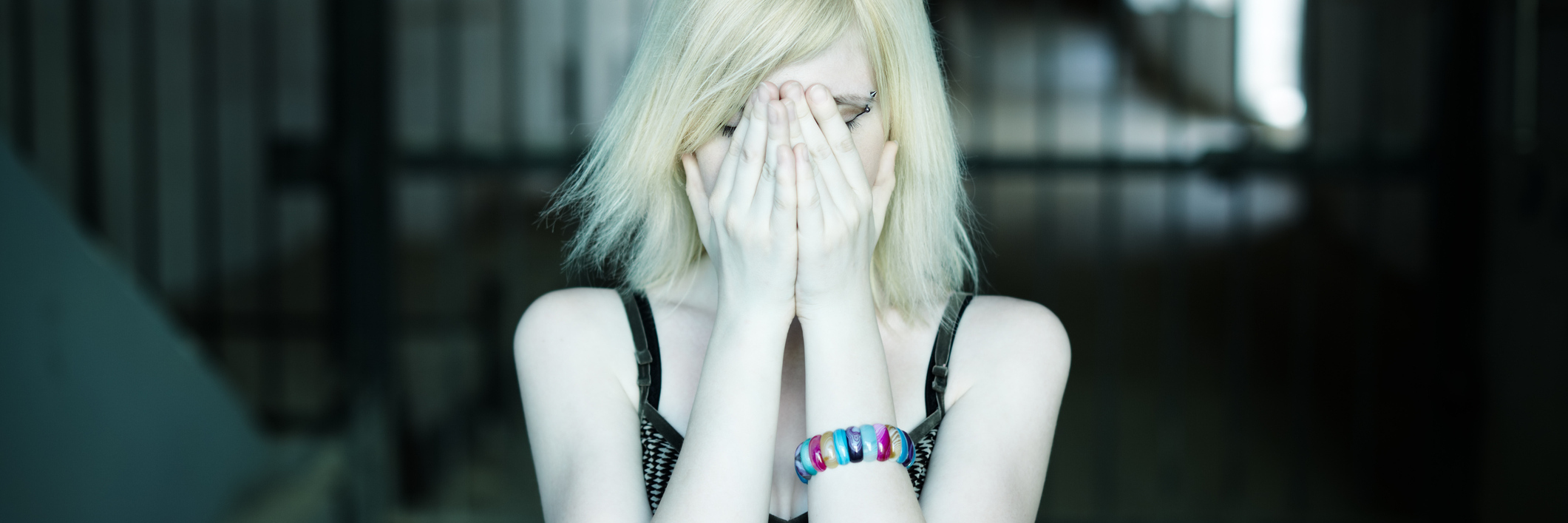 woman in dark hallway with hands covering face and eyes looking upset