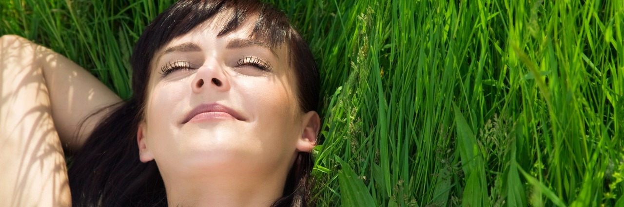 woman lying down on the grass and smiling