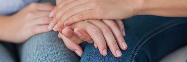 two people touching hands sitting close to one another