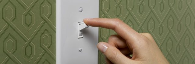 woman with finger to light switch and green wallpaper