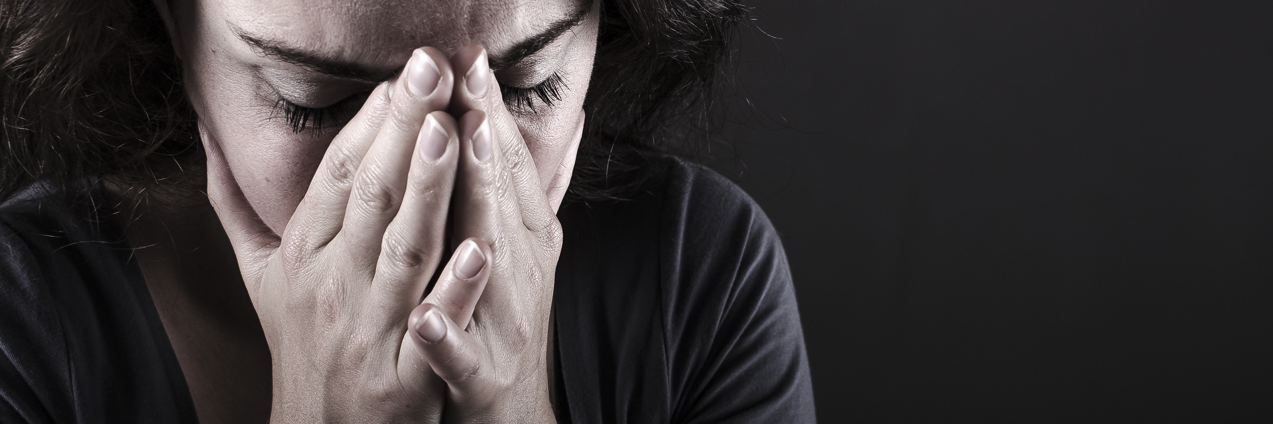 woman on dark background looking scared or depressed with hands covering face